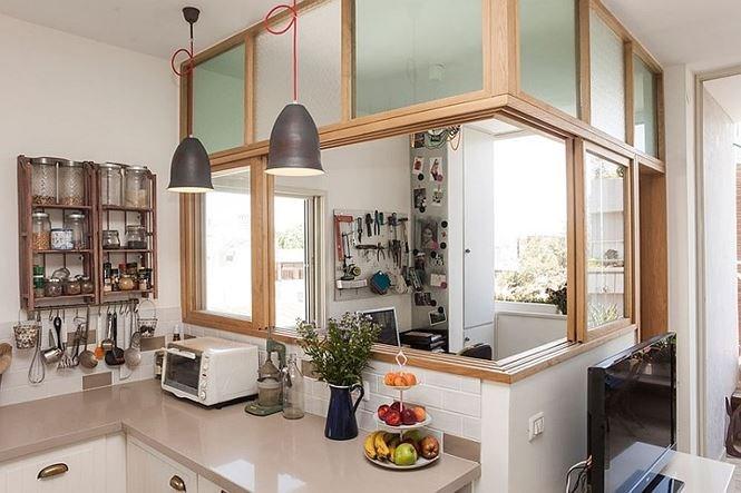 Bàn làm việc tận dụng khoảng hở giữa ban công và nhà bếp, nó ngăn cách với bếp bằng cửa kính để ngăn mùi thức ăn.