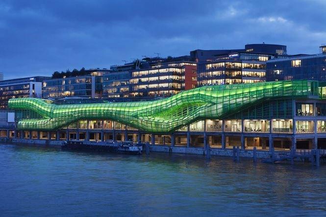 """Kiến trúc """"Thành phố thời trang và thiết kế"""" được xây dựng bên bờ của dòng sông Seine, Paris. Tòa nhà kém đặc sắc trước đây nay thật nổi bật với kiến trúc xanh sáng, hiện đại ở ngay bên ngoài."""
