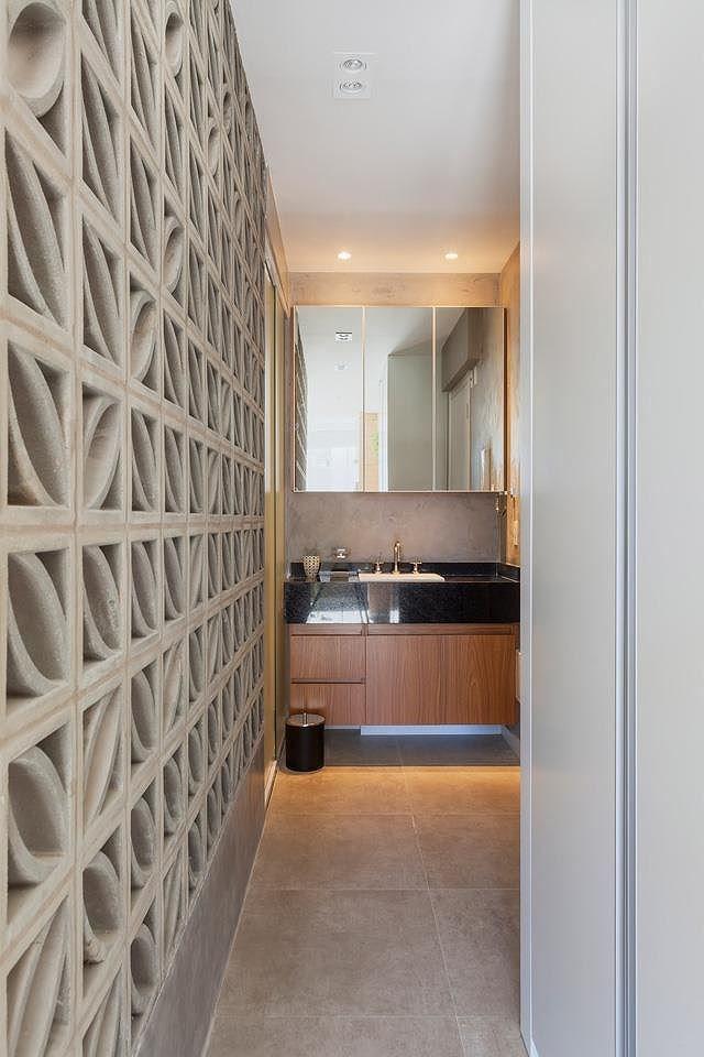 Lối dẫn vào phòng tắm. Bên cạnh lối đi là chiếc tủ cao kịch trần và bức tường gạch lỗ hoạ tiết.