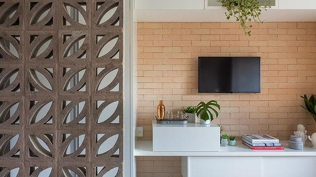 Tivi được gắn trực tiếp trên tường, bên dưới là kệ tủ đơn giản để bày biện một số đồ trang trí nhỏ gọn giúp không gian thêm sinh động hơn.