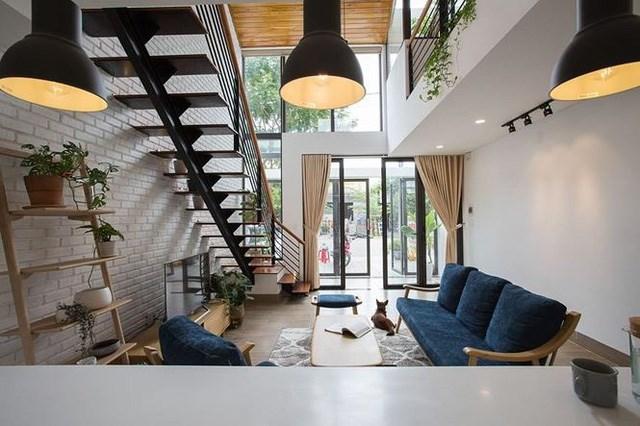 Bước cửa nhà, không gian đầu tiên chính là phòng khách cũng có thể là gara để xe máy. Cầu thang được đặt ngay cạnh lối ra vào, giúp tiết kiệm nhiều không gian hơn cho ngôi nhà.