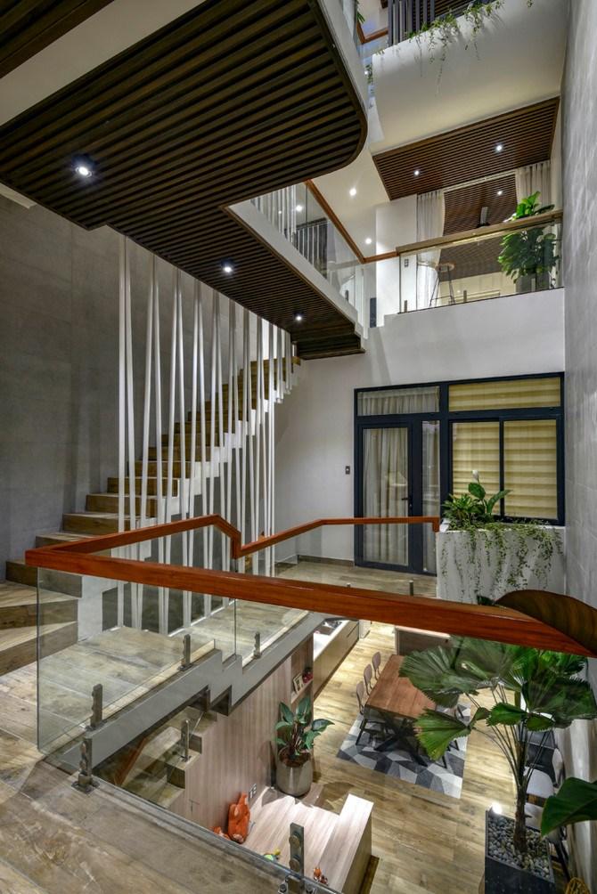 Giải pháp đầu tiên là tạo một không gian thông tầng ở chính giữa nhà, khoảng 11 m2. Cộng thêm diện tích dành cho cầu thang, cả không gian giao thoa là hơn 20 m2, chiếm gần 1/4 diện tích đất xây nhà.