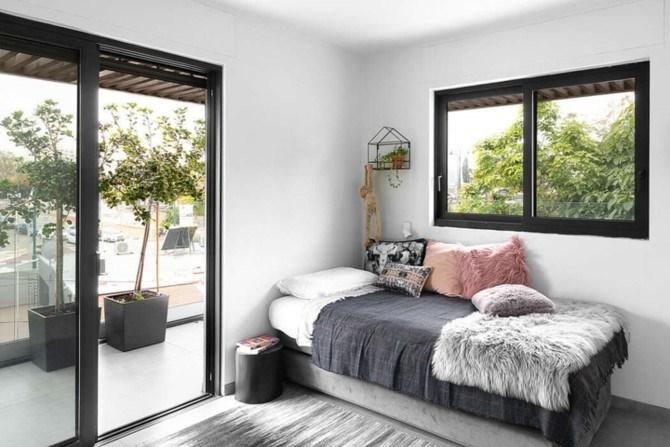 Phòng ngủ trẻ em bố trí đơn giản có cửa thông ra ban công và có thể nhìn thấy khoảng sân phía trước nhà.