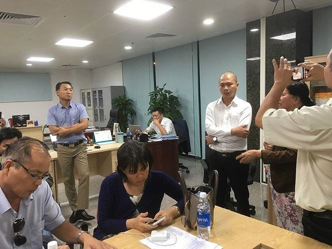 Đại diện chủ đầu tư (áo trắng, bìa phải) trả lời yêu cầu của hàng trăm khách hàng. Ảnh: Thanh Trần.