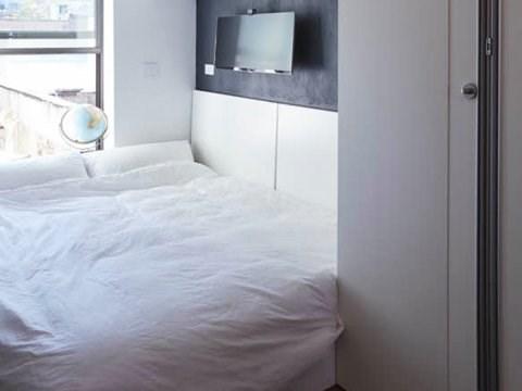 Khi cần thiết, bàn đứng gấp lại để nhường chỗ cho chiếc giường. (Ảnh: Business Insider)