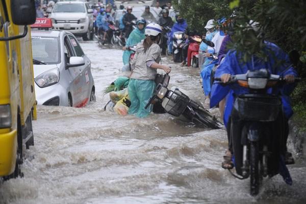 Người dân vất vả vượt qua chỗ ngập đoạn đường gom đại lộ Thăng Long, gần lối vào khu độ thị mới Lê Trọng Tấn - Geleximco (ảnh chụp ngày 21/7/2018) - Ảnh: Khánh Linh
