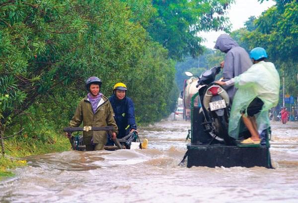 Người dân chỉ còn cách sử dụng dịch vụ vận chuyển thô sơ qua đoạn ngập sâu ở đường gom đại lộ Thăng Long (Ảnh chụp sau trận mưa lớn ngày 21/7/2018) - Ảnh: Khánh Linh