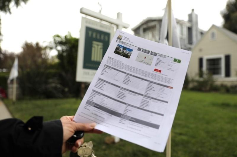 Một phụ nữ cầm tờ quảng cáo bán nhà tại California (Mỹ). Ảnh:Reuters